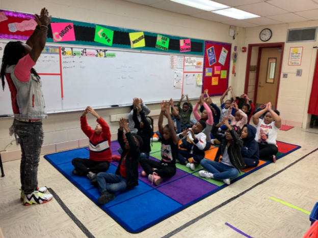 Teacher leading students in a breathing exercise