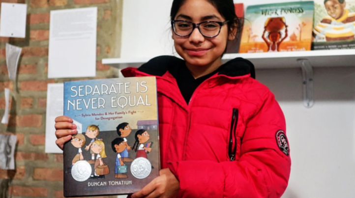 """KIPPster holding the book """"Separate is Never Equal"""""""